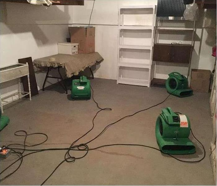 three air movers drying out a room with a bookcase and small table and shelving